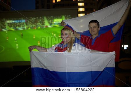 Smiling man and woman with flags of Russia pose against screen with soccer game outdoor at playground.