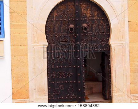 arch doorway with a metal shod door in the Moroccan style