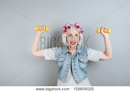 Sport is my life. Glad pretty woman smiling and exercising with dumbbells while standing against isolated gray background.