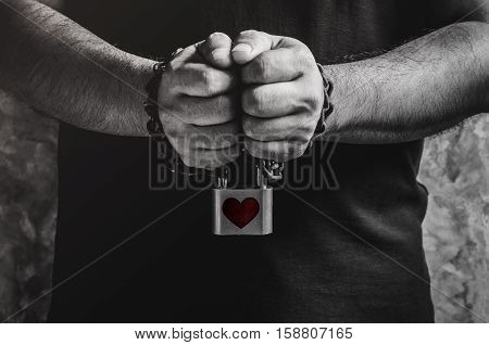 A man of two hands chained with old rusty chain and red heart shape over padlock on concrete wall