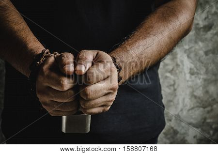 A man of two hands chained with old rusty chain and a padlock on concrete wall