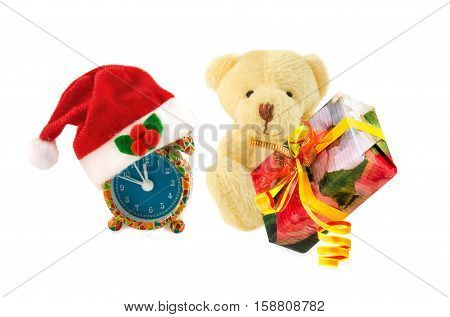 Teddy bear classic soft toy sitting with gift box and alarm clock with Santa hat on white background. Time to make gifts for Christmas and New Year theme.
