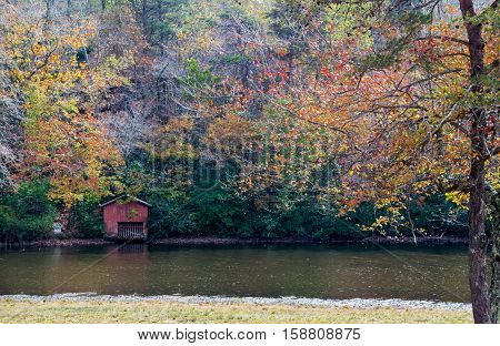 Red boat dock shed near mountain lake in autumn