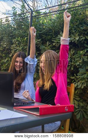 Group of two young girls euphoric entrepreneurs for the results obtained in their company. They are sitting on the terrace table working with the laptop.
