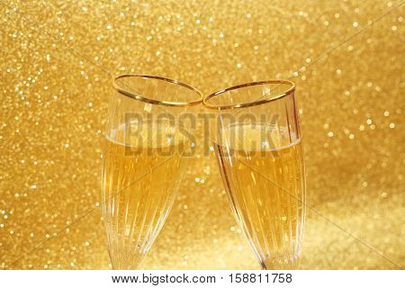 Two clinking glasses of champagne with golden glitter lights on background