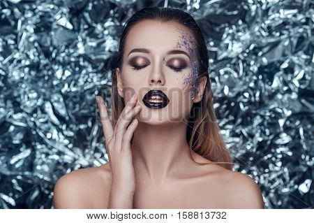 Beautiful young woman with evening shimmering makeup on christmas background. people, beauty, fashion, holiday and magic concept.