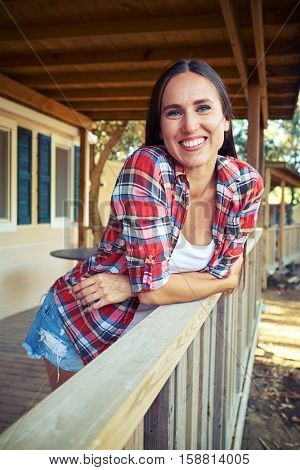 Close-up of the Caucasian woman who is posing at the camera. She is leaning on the handrail near the wooden rest house. Wearing light summer casual checked shirt and denim shorts