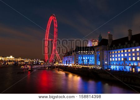 London, UK - November 27, 2016: The London Eye and the Country Hall on the South Bank of the river Thames in London, the Eye is the most popular paid tourist attraction in the United Kingdom.
