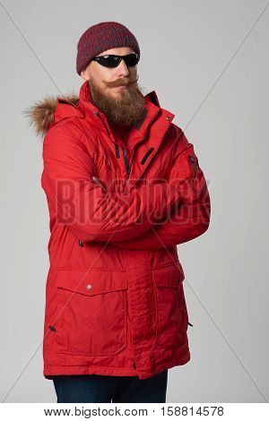 Portrait of a bearded man wearing red winter Alaska jacket and sunglasses, looking out of frame, studio shot