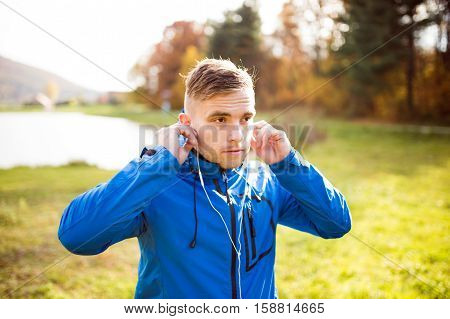 Young handsome hipster runner in blue jacket with earphones listening music outside in colorful sunny autumn nature