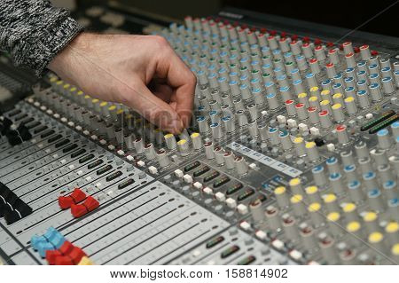 Photography of a sound engineer works with sound mixer