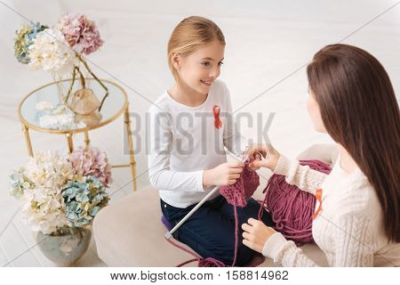 Knitting lesson. Nice attractive caring mother touching the hand of her daughter and looking at her while having a knitting lesson with her