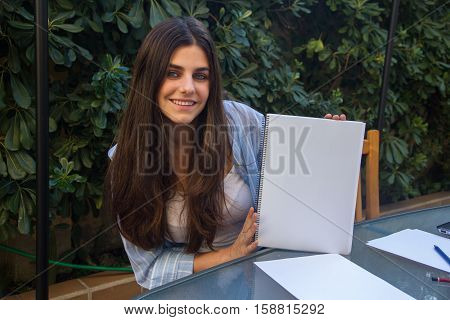 Pretty white entrepreneur girl with blue eyes holding a blank notebook with her hands where you can enclose a text, an outline or an image.