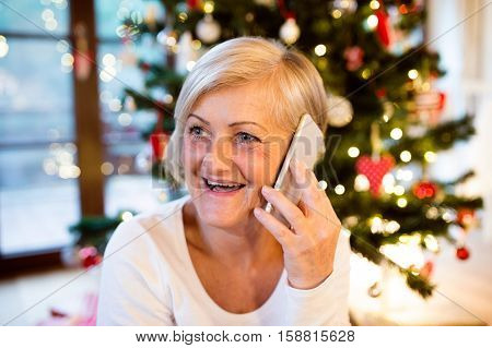 Beautiful senior woman holding smart phone, making phone call, sitting in front of illuminated Christmas tree inside in her house.