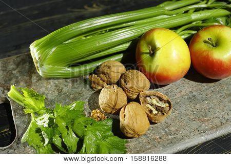 Ingredients for Waldorf salad - celery apples walnotes - fresh and healthy vegetables on granite board.