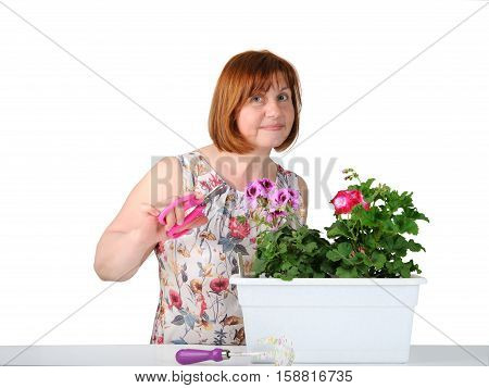 Portrait Of Pretty Middle-aged Woman Caring For Houseplants..