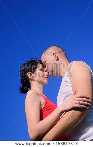 Enamoured pair on the blue sky background