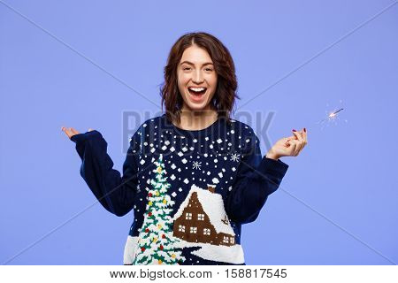 Young cheerful beautiful brunette girl in cosy knited sweater smiling holding bengal lights over blue background. Copy space.