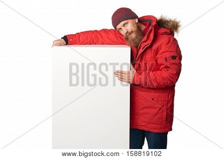 Man wearing red winter jacket embracing big white box banner with copy space, isolated on white