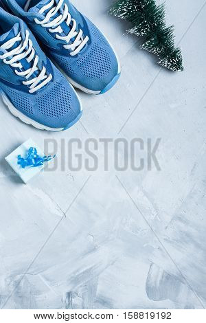 Christmas sport flat lay composition with shoes christmas tree and blue gift box on gray concrete background. Concept сhristmas special for healthy lifestyle and sport. Vertical orientation