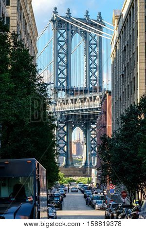 Urban scene in Brooklyn with the Manhattan Bridge at he end of narrow street