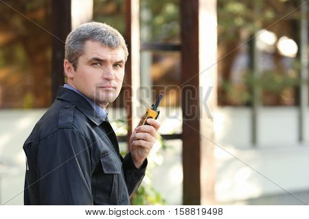 Male security guard near building facade