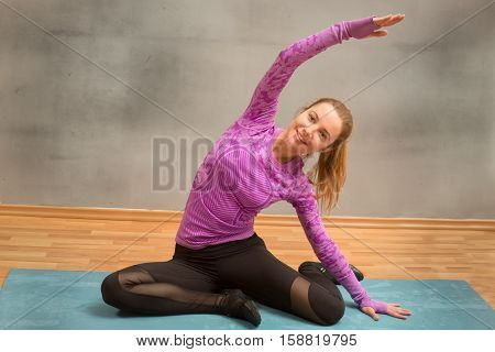 fitness sport training gym and lifestyle concept - smiling woman stretching on mat