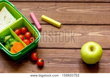 Healthy lunch box for student with juice on wooden background