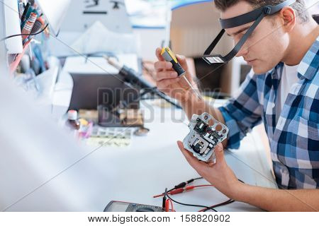 Necessary but hard. Young handsome concentrated man repairing drones chip and using screwdriver while controlling it with electronic tester.