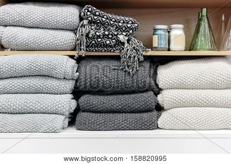 a pile of cotton towels on wood shelf