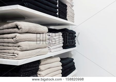 a pile of cotton towels on shelf