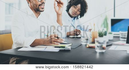Black african businessman explaning business strategy in meeting room.Two young entrepreneurs working together in a modern office.Horizontal wide, blurred background