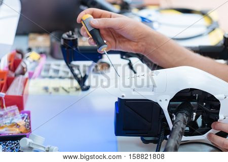 Help of equipment. Close up of hardworking young mans hands using screwdriver while repairing drone and putting details together.