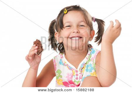 Happy joyful little girl eating chocolate bar for snack isolated on white background
