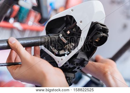 Make it work better. Close up of young mans hands putting together drone parts while working and enjoying his hobby in workroom.
