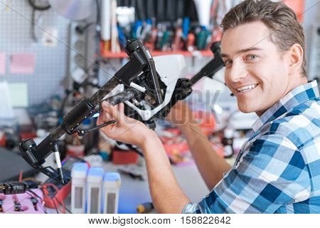 Best worker. Delighted handsome young man holding drone details while sitting in a workroom and smiling
