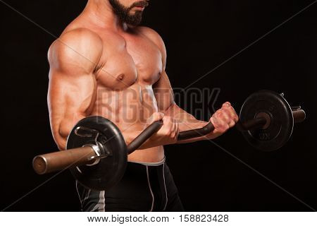 Muscular male athlete is training by lifting the barbell.
