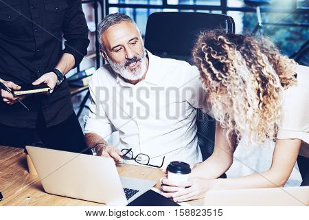 Young team of coworkers making great work discussion in modern office.Bearded man talking with marketing director and assistant manager.Business people meeting concept.Horizontal closeup, blurred