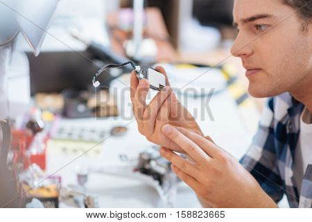 Under control. Serious smart concentrated man discovering chip of a drone attentively while repairing it and spending time in a workroom.