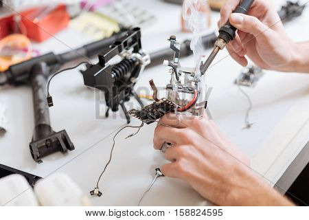 Patience and energy. Detailed close up of mans hands soldering drone chips while using soldering iron while sitting in a workroom.