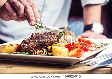 Chef in hotel or restaurant kitchen cooking only hands. Prepared beef steak with vegetable decoration.