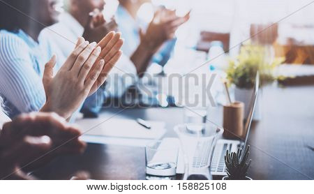 Closeup photo of young business partners applauding to reporter after listening report at seminar. Professional education, work meeting, presentation or coaching concept.Horizontal, blurred background