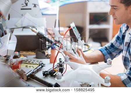 Gather it all. Young handsome hardworking man putting together all drone details while working with mechanism and electronic equipment.