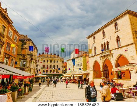 Split, Croatia - May 08, 2014: Tourists walking in the Old City on a cloudy summer day, on May 08, 2014 in Split, Croatia.