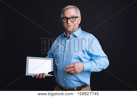 Look here. Smart positive middle-aged male holding tablet in right hand wearing smart clothes keeping glasses on the bridge of nose