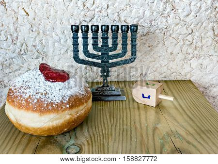 Festive sweet donuts, menorah and dreidels are traditional symbols of Hanukkah holiday