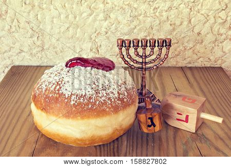 Traditional Jewish sweet donuts, menorah and other religious symbols for Hanukkah holiday. Selective focus. Image toned for inspiration of retro style