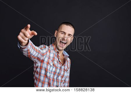 Hey you. Furious young man pointing you and shouting while standing against black background