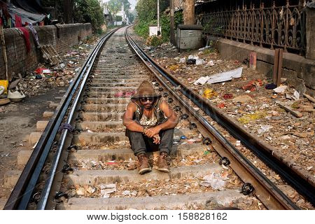 KOLKATA, INDIA - JAN 16, 2013: Young guy sitting on the railroad tracks on January 16, 2013. Third biggest indian city Kolkata with suburbs is home to approximately 14.1 mill.people