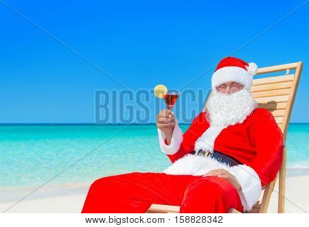 Christmas Santa Claus resting on sunlounger with fresh juice cocktail at ocean sandy tropical beach - New year travel vacation in hot countries concept